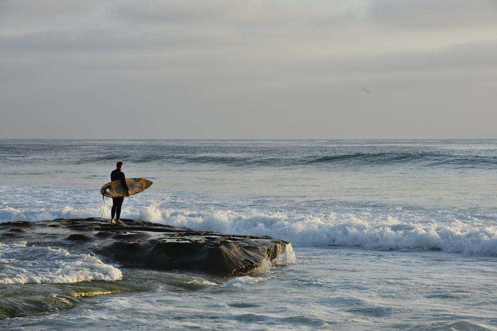 Surfer standing on a rock